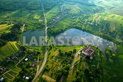 Countryside aerial view on old castle with red roof over the lake