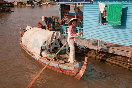 Vietnamese girl in a straw hat with big margins is standing with a huge paddle boat
