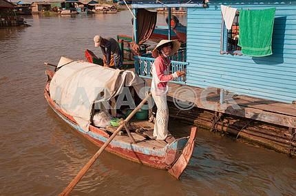 Девушка вьетнамка в соломенной шляпе с большими краями стоит с огромным веслом на лодке
