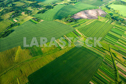 Aerial view on green and yellow parts of fields and countryside