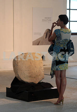 """Girl examines the sculpture at the Biennale in the """"Art arsenal"""""""