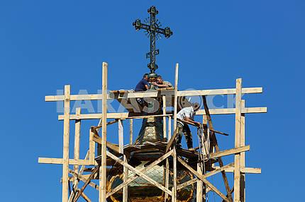 Builders set a cross onto the church