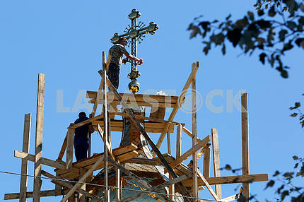 Builders set a cross onto the church