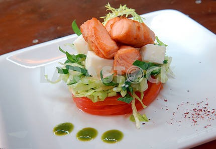 Salad from fresh vegetables with pieces of salmon