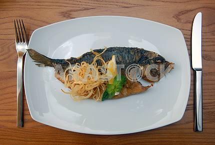 Fried fish with a potato and lemon