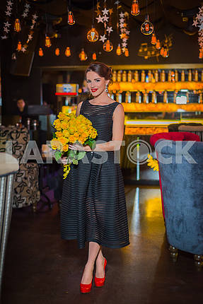 Beautiful brunette woman standing with the yellow roses in her hand, in the restaurant, in black dress and red shoes. Smiling with her red lips