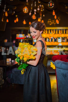 Beautiful brunette woman standing with the yellow roses in her hand, in the restaurant, in black dress and red shoes. Smiling with her red lips, shy like a little girl