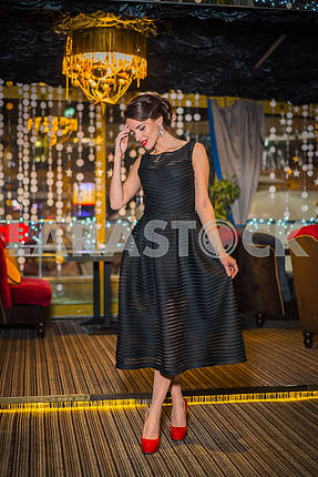 Beautiful brunette woman walking in the restaurant, in black dress and red shoes. Smiling with her red lips, shy like a little girl