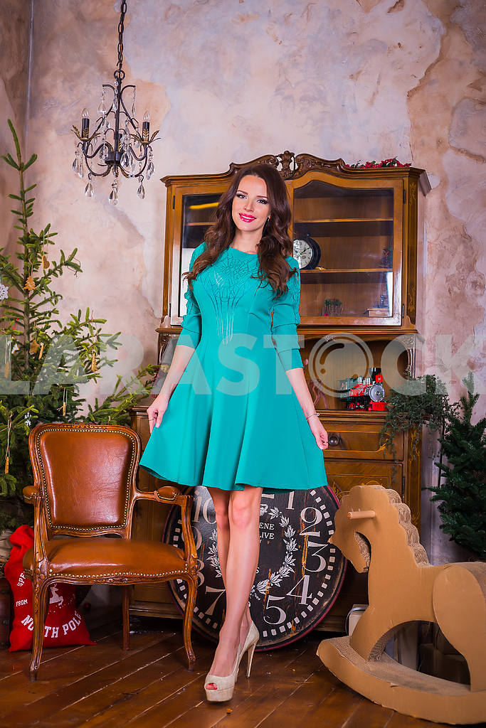 Beautiful brunette woman walking,  among the new year decorations in bright blue dress, smiling — Image 37633