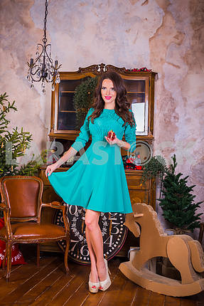 beautiful brunette woman standing with present in her hands,  among the new year decorations in bright blue dress, smiling