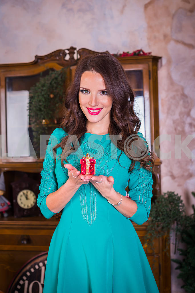 Portrait beautiful brunette woman walking with present in her hands,  among the new year decorations in bright blue dress, smiling — Image 37635