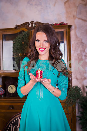 Portrait beautiful brunette woman walking with present in her hands,  among the new year decorations in bright blue dress, smiling