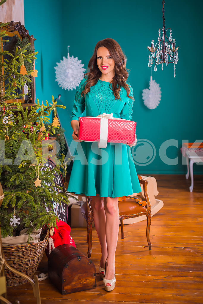 Beautiful brunette woman walking with present in her hands,  among the new year decorations in bright blue dress, smiling — Image 37637