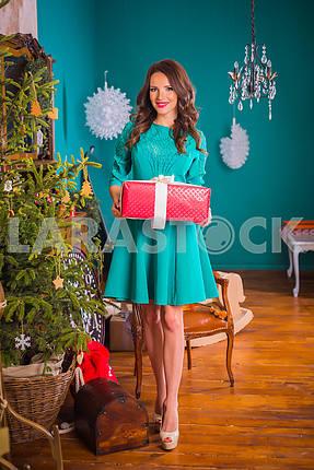 Красивая брюнетка женщина, идущая с настоящим в ее руках, в том числе новогодние украшения в ярко-синем платье, улыбаясь