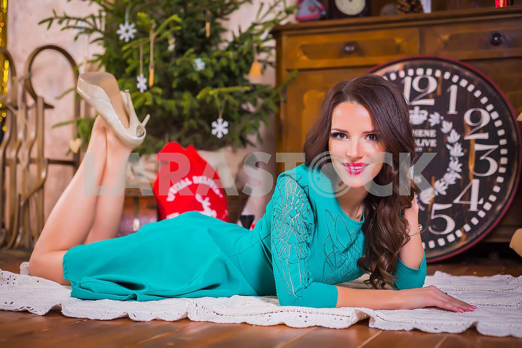 Красивая брюнетка женщина, лежа на полу среди новых лет украшения в ярко-синем платье, улыбаясь — Изображение 37640