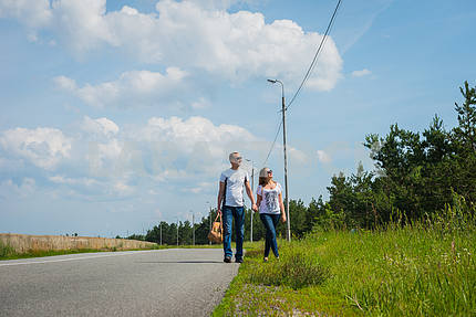 a love story couple traveling with bag, walking on the sunny day, weared on jeans, blue sky and white clouds on the background