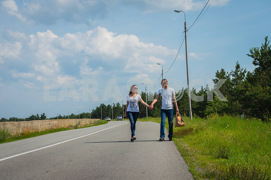 A love story couple travelling with bag, walking on the sunny day, weared on jeans, blue sky and white clouds on the background — Image 37867