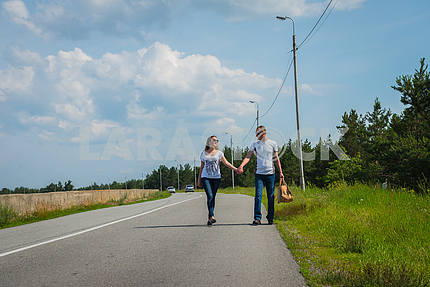 a love story couple travelling with bag, walking on the sunny day, weared on jeans, blue sky and white clouds on the background