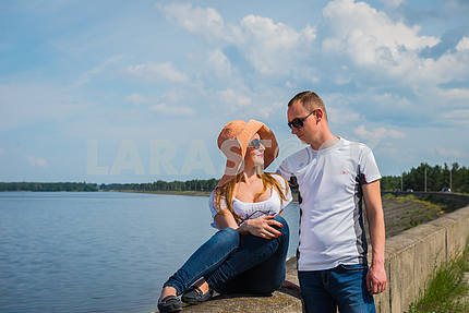 A love story couple travelling, resting near the water, looking into each other, on the sunny day, weared on jeans, blue sky and white clouds on the background