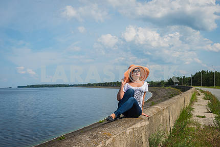 Woman traveling, resting near the water, looking into the sky, on the sunny day, weared on jeans, blue sky and white clouds on the background, weared on sunhat
