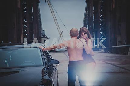Красивая блондинка девушка, стоя сексуально на незавершенные мосту, с мужчинами топлесс назад и автомобиль, в черном корсете в ветреный день, серые облака, держа друг друга