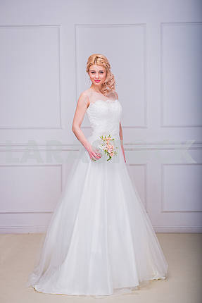 Blonde beautiful bride in long wedding dress with wedding bouquet - shooting in studio. curly hair