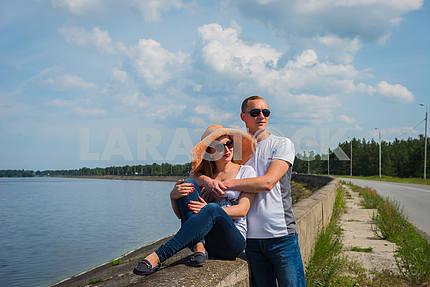 Пара в любви, охватывающей, сидели, держась руками, рядом с водой в солнечный день, голубое небо с длинными белыми облаками на заднем плане. мужчины и женщины улыбаются, счастливые