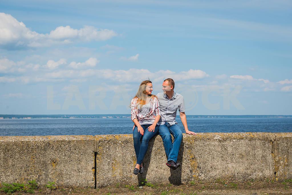 Пара в любви, охватывающей, сидели, держась руками, рядом с водой в солнечный день, голубое небо с длинными белыми облаками на заднем плане. мужчины и женщины улыбаются, глядя друг на друга — Изображение 37900