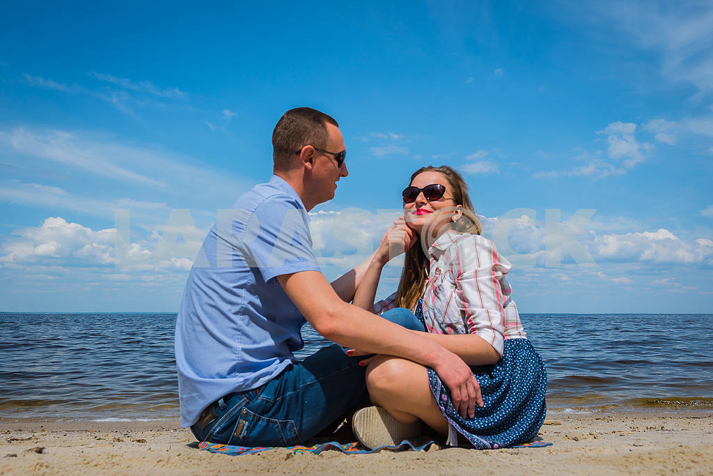 A loving couple sittingon the beach, near the water, playing with each other, blue sky on the background, sunny day, wide angle, long white clouds — Image 37975