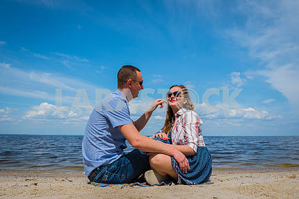 a loving couple sittingon the beach, near the water, playing with each other, blue sky on the background, sunny day, wide angle, long white clouds