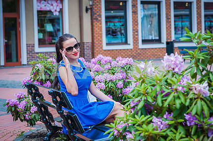 beautiful brunette woman in sunglasses, sitting on the bench near the bushes of purple flowers, resting, posing in blue short  dress