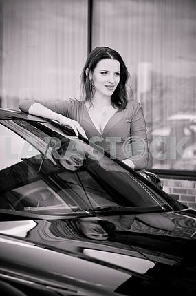 beautiful brunette standing near the car, her reflection in the glass, looking to the right, black and white