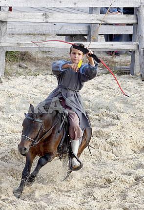 Девочка с луком скачет верхом на лошади