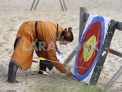Assistant Girl near the target archery shooting evaluates results