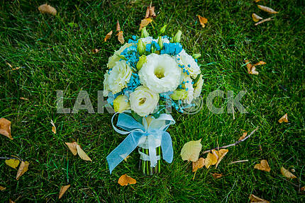Wedding bouquet laying on the green grass with yellow and orange leaves near  bouquet made of white and blue flowers