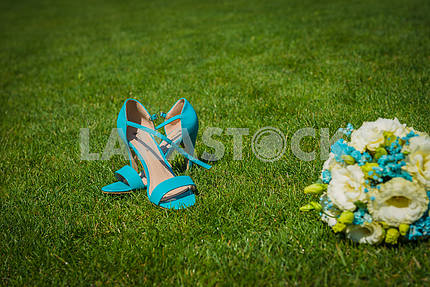 Wedding bouquet laying at the green grass adn the sandals standing near  all in blue colors