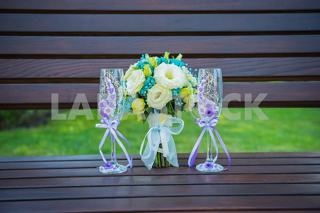 Wedding bouquet with stemware (a glass of champagne), in blue and violet colors, glasses decorated with flowers, standing on the bench, flat lay — Image 38434