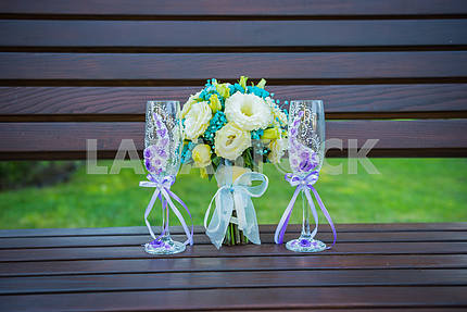 wedding bouquet with stemware (a glass of champagne), in blue and violet colors, glasses decorated with flowers, standing on the bench, flat lay
