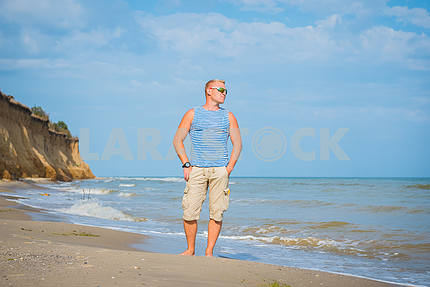 A man standing on the beach looking far away, dressed into frock in sunglasses. sea on the background, breakage and blue sky with white clouds, Black Sea, sunny day