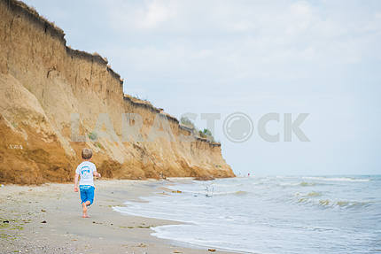 A child running out along the shore of the Black Sea. in blue shorts and white t-shirt. sea on the background breakage and light blue sky, little boy running, having fun playing in the sand on a beach