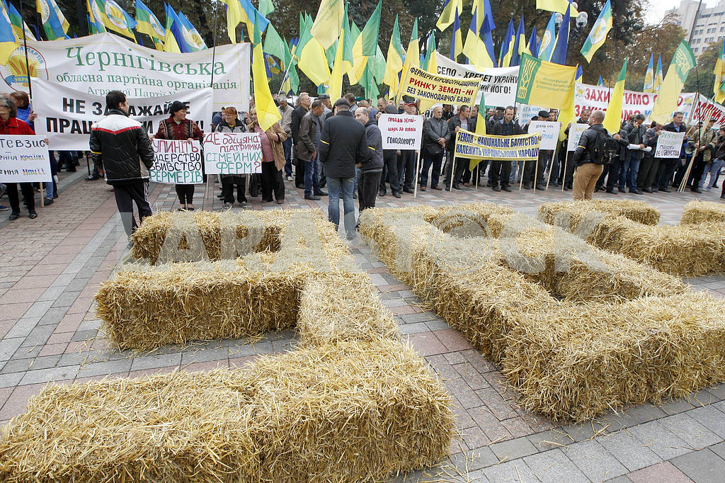 Farmers hold placards near hay lined in the form of numbers — Image 38544