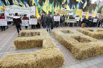 Farmers hold placards near hay lined in the form of numbers