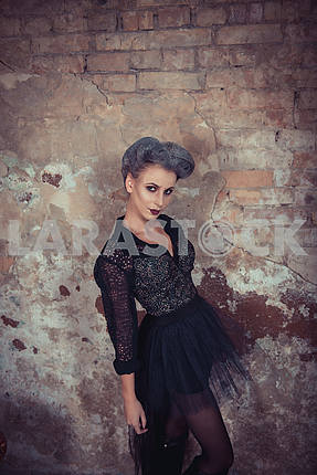 Woman dressed like a vampire - for halloween party, standing near the old brick wall . Short black tulle-skirt on a vampire-girl. looking angry like a devil. looking at you cunningly