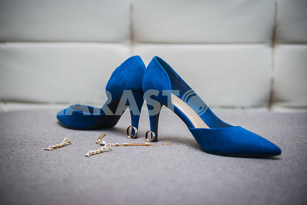 Beautiful bride shoes with a gorgeous earrings on the sofa girl in shoes with high heels pair of blue shoes with heels shoes — Image 38643