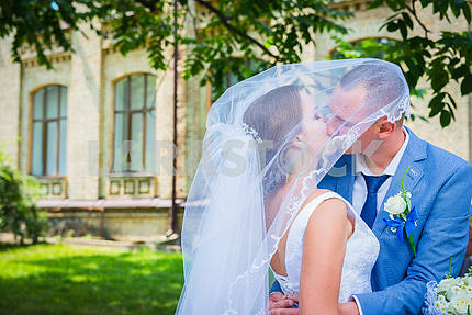 Bride and groom kisses tenderly in the shadow of a flying veil