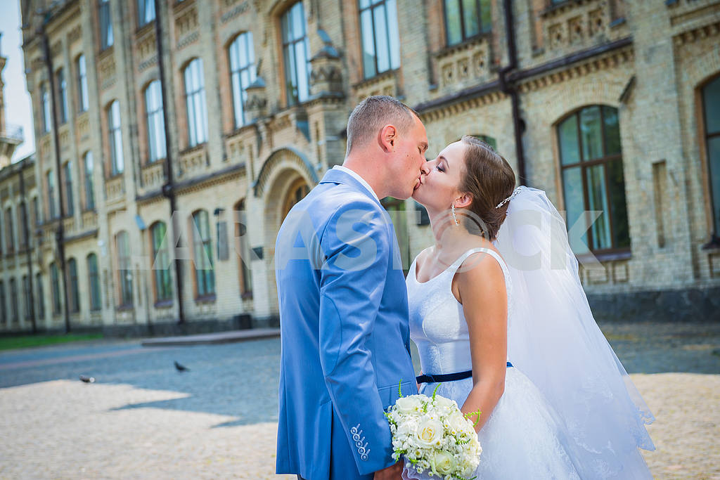 Bride and groom, on the street, green tree and architecture building on the background, kissing each other, wedding day — Image 38647