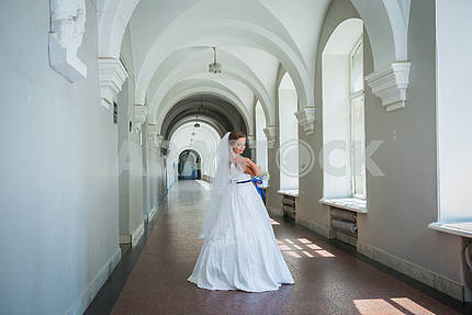 A bride standing in the hall, in a long wedding dress, with the veil  and blue ribbon on her waist, wedding  day