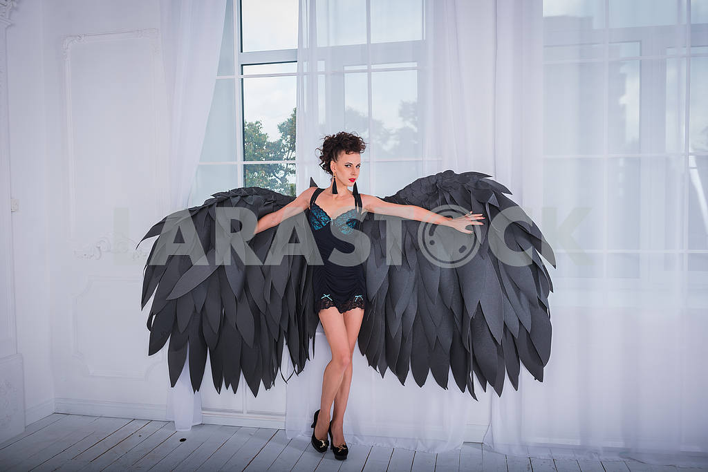 Brunette woman - black angel with the big wings, red lips, black short suit, in white room  standing near the window — Image 38824