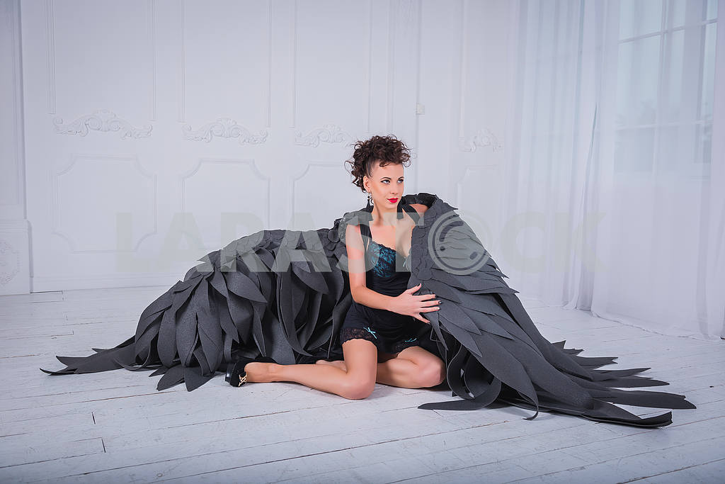 Brunette woman - black angel with the big wings, red lips, black short suit, in white room  sitting on the floor — Image 38825