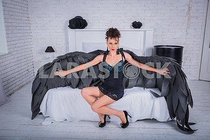 brunette woman - black angel with the big wings, red lips, black short suit, in white room
